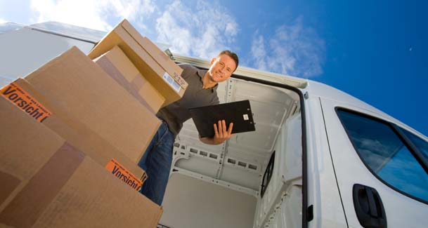 An image showing a white Sky Van Hire van and driver, unloading a stack of cardboard boxes.