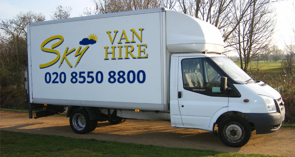 An image of a white Sky Van Hire Luton Body with tail lifet van outside on the road.
